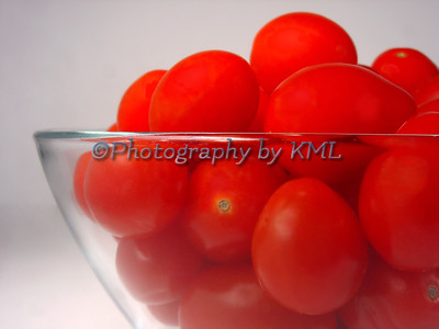 a clear glass bowl filled with cherry tomatoes
