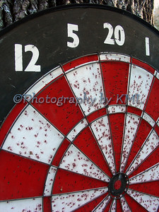 a well used red and white dart board