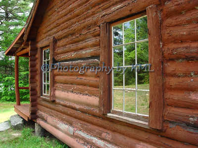 reflections in the window of an old log cabin
