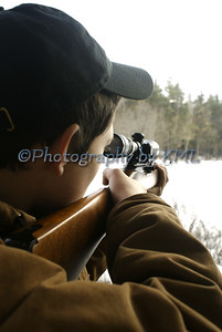 a teen boy aiming a hunting rifle