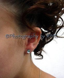 a blue earring in a pierced ear