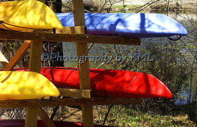 colorful kayaks stacked on a rack