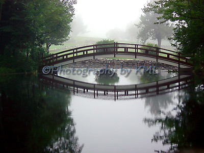 a small foot bridge in the early morning fog