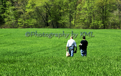 father and son walking in a green field