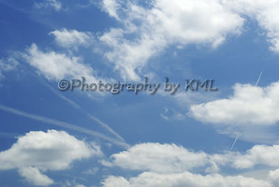contrails stretching across a blue sky with white clouds