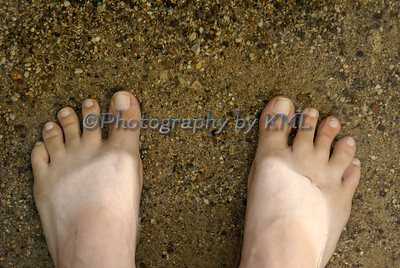 bare feet in the water and sand