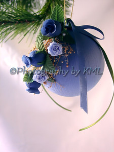 a handmade christmas ornament with flowers hanging from the tree