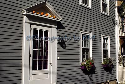 window boxes and pumpkins above the door