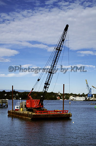 a red crane on a barge in the ocean
