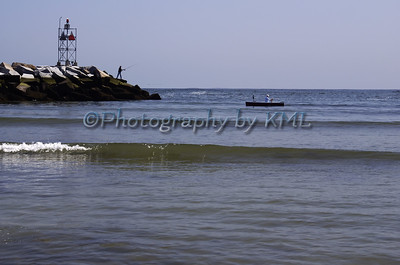 A boy fishing on the rocks and a fishing boat in the harbor